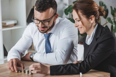 happy financiers stacking coins on table in office