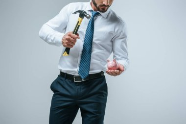 cropped image of financier breaking piggy bank with hammer isolated on grey