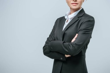cropped image of businesswoman standing with crossed arms isolated on grey