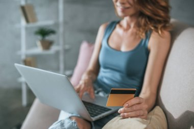 cropped image of woman shopping online with laptop and credit card at home