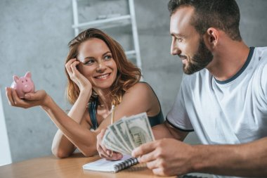 happy couple planning family budget and looking at each other in living room