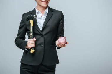 cropped image of financier holding hammer and piggy bank isolated on grey