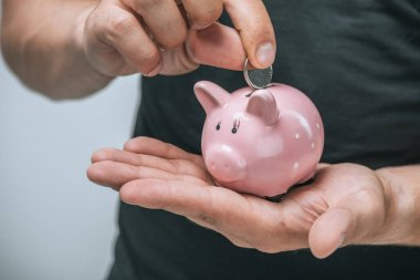 cropped image of man putting coin in pink piggybank isolated on grey