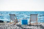 zadní pohled na pruhovanou lenošky a chladnější n písečná pláž