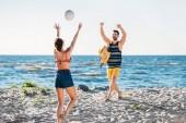 boldog, fiatal pár homokos strandon játszott röplabda