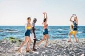 Fotografia young multiethnic friends playing volleyball on sandy beach