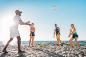 happy young multiethnic friends playing volleyball on sandy beach