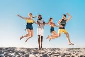 Happy mladých mnohonárodnostní přátelé drží za ruce a skákání v písečná pláž
