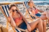 Fotografie krásné šťastné mladé ženy sedí na písečné pláži v lenošky