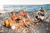 beautiful young women resting on beach chairs and african american man playing guitar