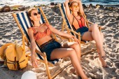 beautiful young women resting on chaise longues on sandy beach
