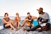 Fotografie happy young multiethnic friends spending time together on sandy beach