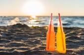 Detailní pohled skleněných lahví s osvěžujícími nápoji a brčka na písečné pláži při západu slunce
