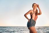 krásná šťastná mladá žena v sluneční brýle, plavky a džínové šortky, usmála se na kameru na pláži při západu slunce
