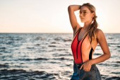 krásná mladá žena v sluneční brýle, plavky a džínové šortky, koukal na pláži při západu slunce