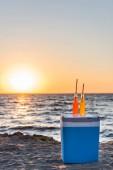 skleněné lahve s letní nápoje a brčka na chladič na písečné pláži při západu slunce