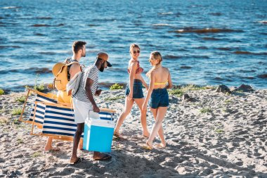 high angle view of young multiethnic friends with beach items walking on sandy sea coast