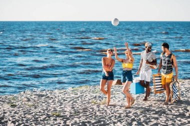 happy young multiethnic friends playing with ball while walking on sandy beach