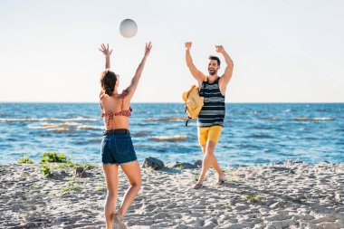 happy young couple playing volleyball on sandy beach