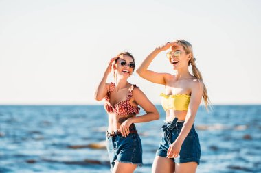 Happy young women in sunglasses walking together on beach stock vector