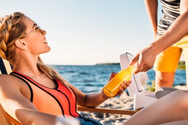 cropped shot of man giving glass bottle with refreshing drink to beautiful woman on beach