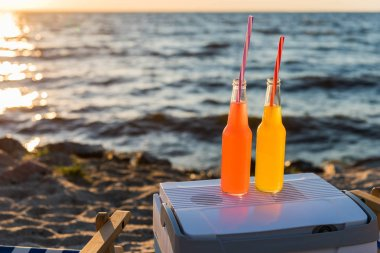close-up view of summer drinks with straws and cooler on sandy beach at sunset
