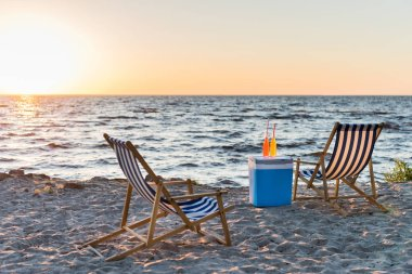 summer drinks on cooler and chaise lounges on sandy beach at sunset