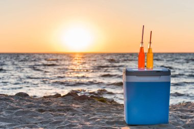 glass bottles with summer drinks and straws on cooler at sandy beach