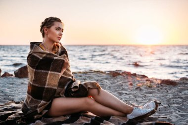 Beautiful pensive young woman sitting wrapped in plaid and looking at majestic sunset at sea stock vector