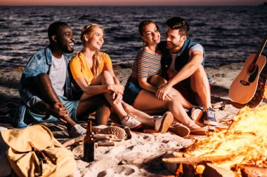 happy young multiethnic friends talking and spending time together on sandy beach at sunset