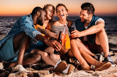 Happy young people clinking glass bottles with drinks while spending time together on sandy beach at sunset stock vector