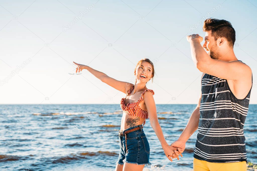 happy young couple holding hands and looking away while walking together on beach