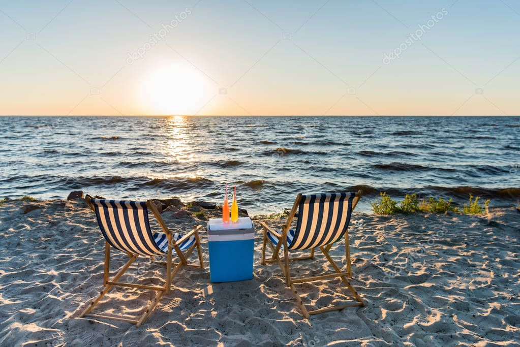 summer beverages on cooler and chaise lounges on sandy beach at sunset