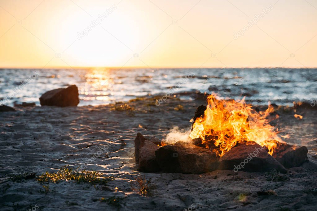 bonfire on sandy sea coast at majestic sunset