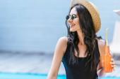 Fényképek mosolygó fiatal nő a gazdaság üveg frissítő ital és nézett medence fürdőruha