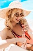 Fotografie krásná usměvavá mladá žena v plavky a sluneční brýle, pití letní nápoj u bazénu