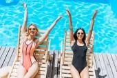 pohled z vysokého úhlu úsměvu mladých žen na lehátka u bazénu