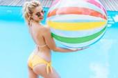 krásná usměvavá blondýnka v bikinách a brýle drží nafukovací míč na bazénu