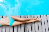 Schnappschuss einer jungen Frau im Bikini, die in der Nähe eines Schwimmbades liegt