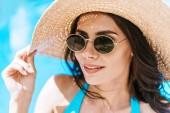 Krásná brunetka žena v sluneční brýle a slamák se usmívá na bazénu