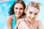 krásné šťastné mladé přítelkyně se usmívá na kameru v blízkosti bazén