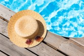 close-up view of wicker hat and sunglasses near swimming pool