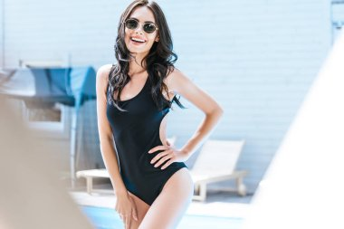 selective focus of beautiful brunette girl in swimsuit and sunglasses smiling at camera at poolside