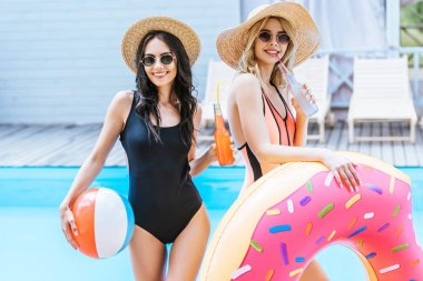 beautiful young women holding bottles with summer drinks and beach items and smiling at camera near swimming pool