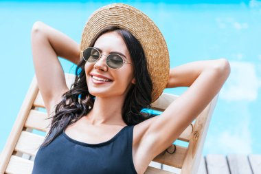 beautiful young brunette woman in swimsuit, straw hat and sunglasses resting with hands behind head at poolside