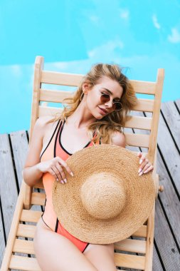 High angle view of beautiful woman in swimsuit and sunglasses holding straw hat and resting on chaise lounge near pool stock vector