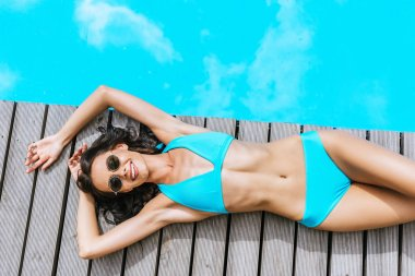 top view of beautiful smiling young woman in bikini and sunglasses resting near pool