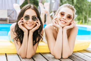 beautiful young women lying on inflatable mattress and smiling at camera at poolside