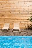 prázdné útulné lenošky poblíž bazén s průzračnou vodou