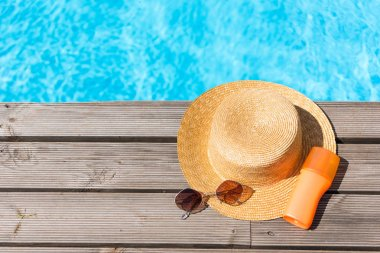 top view of wicker hat, sunglasses and sunscreen near swimming pool